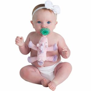 Girl baby in white diaper with unicorn rattle in mouth and white bow on head
